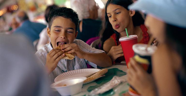 Jóvenes comiendo en establecimiento de comida rápida